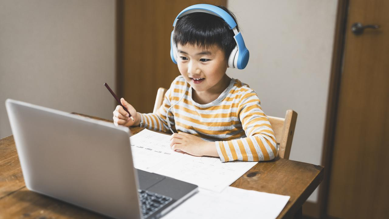 boy wearing headphones at computer