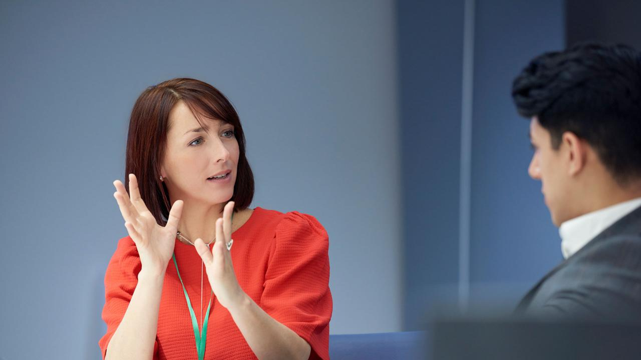 woman using hand gestures to explain something to man sitting across from her at conference table
