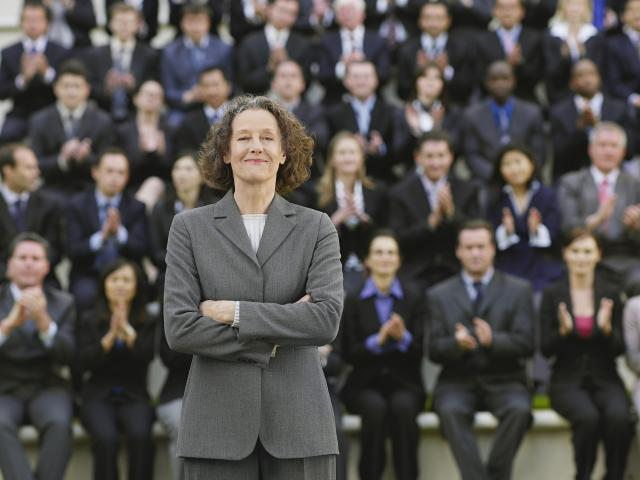 Woman in a business suit standing with a applauding crowd behind her