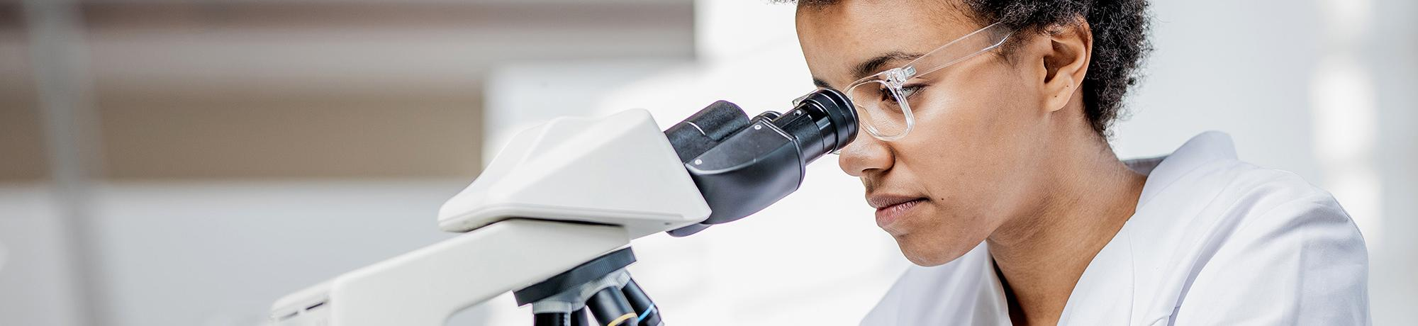 scientist in lab looking in microscope